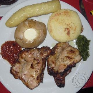 Tasty Colombian dish. Chicken, potato, arepa, platano & sauces